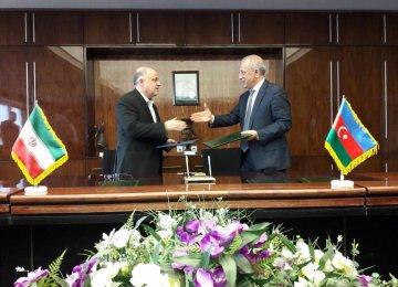 Iran's Deputy Minister of Energy Homayoun Haeri (L) and his Azerbaijani counterpart Natiq Abbasov signed an agreement in Tehran on April 12.
