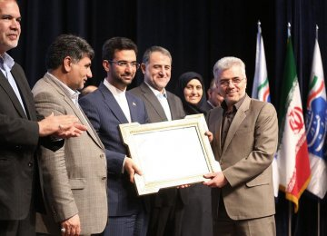 ICT Minister Mohammad Javad Azari-Jahromi (3rd L) presented an award to Hossein Fallah Josheqani, the head of Communications Regulatory Authority, in Tehran on March 12.