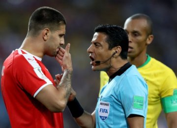 Alireza Faghani talks to Serbia's Aleksandar Mitrovic during the Wednesday Group B match between Brazil and Serbia.