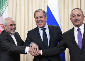 Mohammad Javad Zarif (L), Sergey Lavrov (C) and Mevlut Cavusoglu shake hands at the end of a joint press conference following their talks in Moscow on April 28.