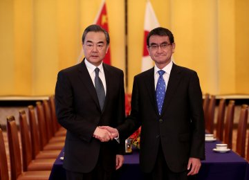 Chinese Foreign Minister Wang Yi (L) shakes hands  with Japan's Foreign Minister  Taro Kono in Tokyo, April 15.