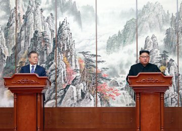 South Korean President Moon Jae-in and North Korean leader Kim Jong-un walk during a luncheon on Sept. 21.