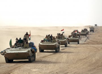 Iraqi forces and members of the Hashed al-Shaabi advance towards the city of al-Qaim, in western Anbar province, as they fight against remnant pockets of IS.