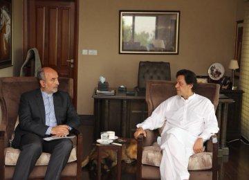 Pakistan Tehreek-e-Insaf Chairman Imran Khan (R) talks with Iranian Ambassador Mehdi Honardoost in Islamabad on Saturday.