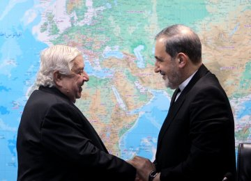 Syrian Foreign Minister Walid Muallem (L) shakes hands with Ali Akbar Velayati, a foreign policy advisor to the Leader of Islamic Revolution, in Tehran on Jan. 1.