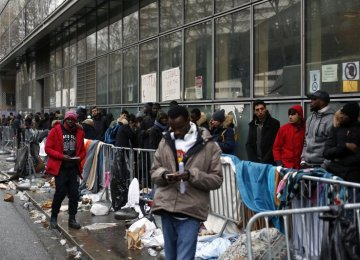 Migrants queue outside a facility to apply for asylum,  in Paris, Dec. 21.