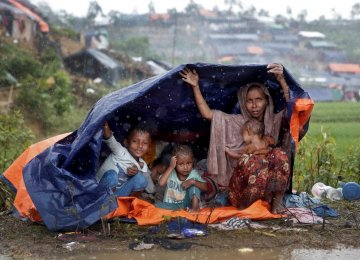 Rohingya refugees shelter from the rain in a camp in Cox's Bazar, Bangladesh, September 17.