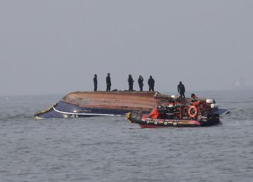 South Korean Coast Guard officers try to rescue a capsized fishing boat which collided with a refueling vessel in the waters off Incheon, South Korea on Dec. 3.