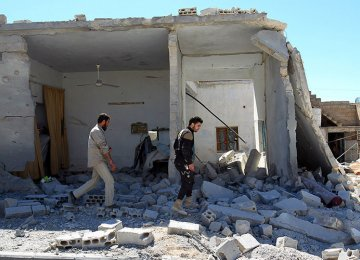 Civil defense members inspect the damage at a site hit by airstrikes in the town of Khan Sheikhoun, Syria, on April 5.