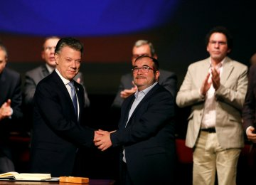 Colombia's President Juan Manuel Santos and Marxist FARC rebel leader Rodrigo Londono, known as Timochenko, shake hands after signing a peace accord in Bogota, Colombia November 24, 2016.