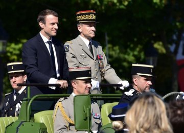 French President Emmanuel Macron (L) and former armed forces chief General Pierre de Villiers ride aboard a command car during the Bastille Day military parade in Paris on July 14.