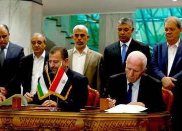 Head of Hamas delegation Saleh Arouri (L) and Fatah leader Azzam Ahmad sign a reconciliation deal in Cairo, Egypt on October 12.