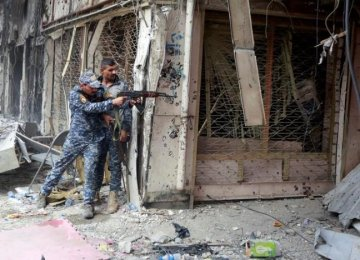 A member of the Iraqi Federal Police opens fire against IS militants in the Old City of Mosul, Iraq, on July 7.