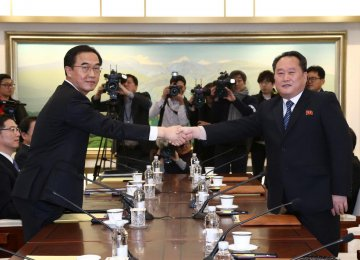 Head of the North Korean delegation, Ri Son Gwon (R), shakes hands with his South Korean counterpart, Cho Myoung-gyon, during their meeting at the truce village of Panmunjom on January 9.