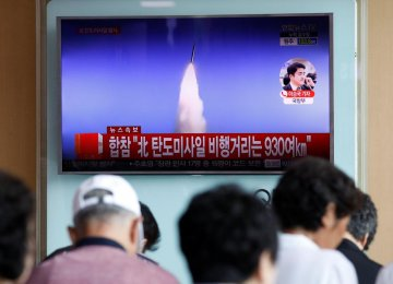 People watch a TV broadcast of a news report on North Korea's ballistic missile test, at a railway station  in Seoul, South Korea, July 4.