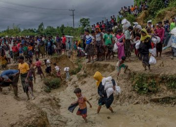 A crowd of Rohingya walk carrying aid through  a muddy refugee camp.