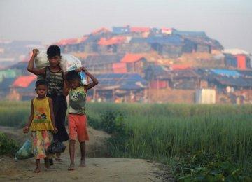 Rohingya refugee children carry supplies through Balukhali refugee camp near Cox's Bazar, Bangladesh, on October 23.
