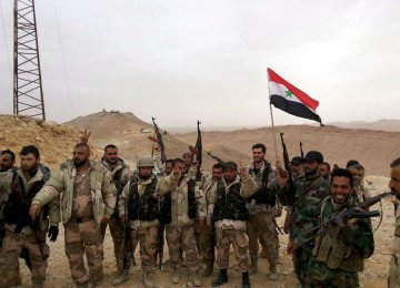 Forces loyal to Syria's President Bashar al-Assad flash victory signs and carry a Syrian national flag on the edge  of the historic city of Palmyra (File Photo)