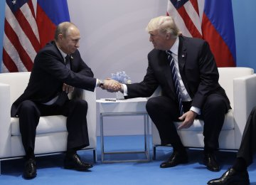 US President Donald Trump (R) shakes hands with Russian President Vladimir Putin during their meeting  on the sidelines of the G20 summit in Hamburg on July 7.