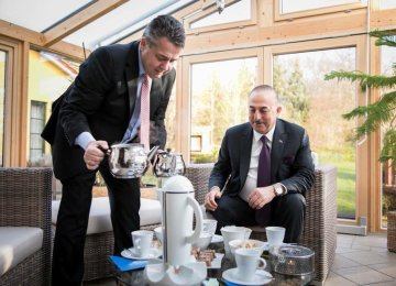 German Foreign Minister Sigmar Gabriel serves his Turkish counterpart, Mevlut Cavusoglu,  from a traditional Turkish teapot.