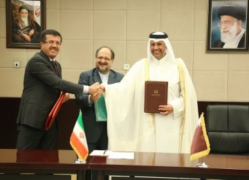 Turkey's Economy Minister Nihat Zeybekci (L) and his Qatari counterpart Ahmed bin Jassim bin Mohammed Al Thani (R) signed the transportation deal with Iran's Minister of Industries, Mining and Trade Mohammad Shariatmadari in Tehran on Nov. 26.