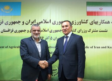 Iran's Minister of Agriculture Mahmoud Hojjati (L) shakes hands with Kazakhstan's Deputy Prime Minister and Minister of Agriculture Askar Myrzakhmetov in Tehran on Sunday.
