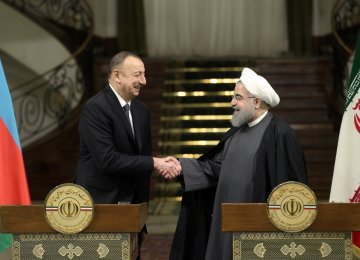 Azerbaijani President Ilham Aliyev (L) shakes hands with Iran's President Hassan Rouhani in Tehran  on March 5.
