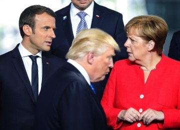 Donald Trump (C) walks past Emmanuel Macron (L) and Angela Merkel on his way to his spot for a family photo during the NATO summit in Brussels, Belgium, on May 25, 2017. (File Photo)