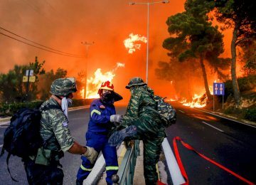 Firemen and soldiers escape from spreading flames near Athens.
