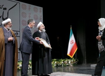 Silvia Balatti from University of Kiel, Germany,(R) receives her award from President Hassan Rouhani (C)  and Culture Minister Seyyed Abbas Salehi.