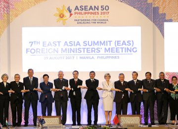 Foreign ministers from Southeast Asia and their dialogue partners link arms during the group photo at the start of the 7th East Asia Summit Foreign Ministers' Meeting and its dialogue partners  as part of the 50th ASEAN regional security forum in Manila on August 7.