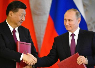 Xi Jinping (L) and Vladimir Putin have agreed to raise the share  of ruble-yuan trade settlements.