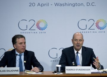 Argentina's Treasury Minister Nicolas Dujovne (L), accompanied by Argentina's Central Bank Governor Federico Sturzenegger speak at a news conference after the G20 meeting on Friday.