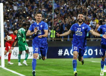 Esteghlal players celebrate their second goal against Al Rayyan at Tehran's Azadi Stadium.