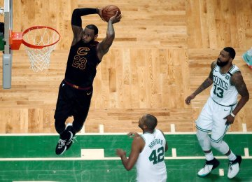 Cleveland Cavaliers forward LeBron James soars to dunk in front of Boston Celtics players.