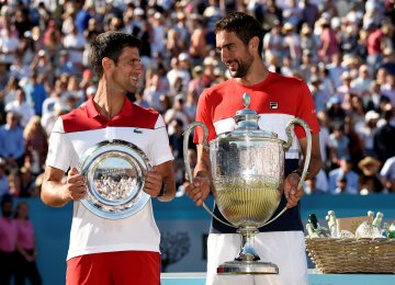 Marin Cilic (R) poses with the trophy after winning the final against Novak Djokovic on Sunday.
