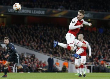 Arsenal's Welsh midfielder Aaron Ramsey scores his second and his team's third goal with this flick during the UEFA Europa.
