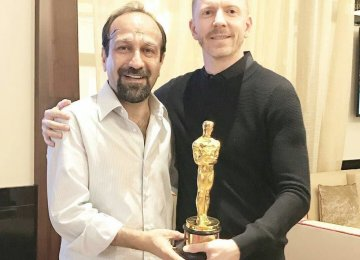 Asghar Farhadi (L) and Alexandre Mallet-Guy with the Oscar statuette for 'The Salesman'