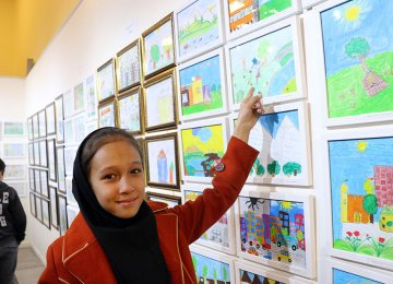 A young girl shows her painting at the exhibit.