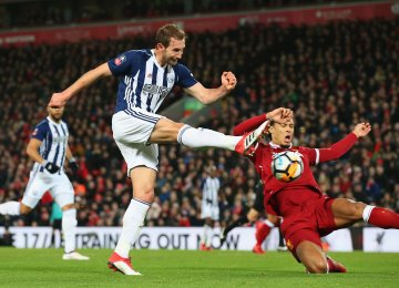 Craig Dawson of West Bromwich Albion takes a shot past Virgil van Dijk of Liverpool in the build up to an own goal scored by Joel Matip of Liverpool.