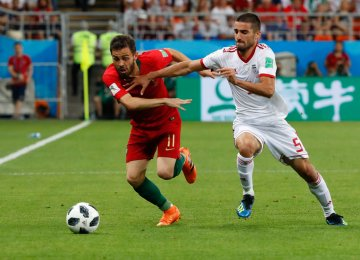 Milad Mohammadi (R) vies for the ball with Bernardo Silva during Iran-Portugal match in FIFA World Cup Russia.