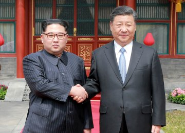 Chinese President Xi Jinping (R) and North Korean leader Kim Jong-un in Beijing on March 27.