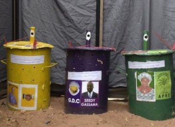 Gambians vote by dropping a marble into a drum