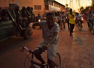 A boy rides a bike near a Senegalese vehicle, as ECOWAS soldiers arrive at the statehouse in Banjul.