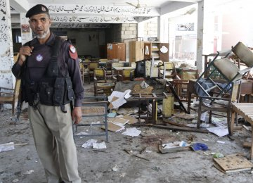 A Pakistani police officer inspects the scene of a previous terror attack.
