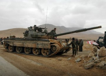 Syrian fighters take position as they advance to retake Palmyra on March 2.