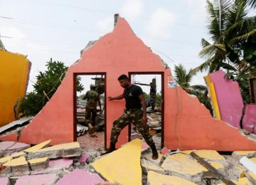 A member of the military inspects a damaged house  in Colombo, Sri Lanka, on April 15.