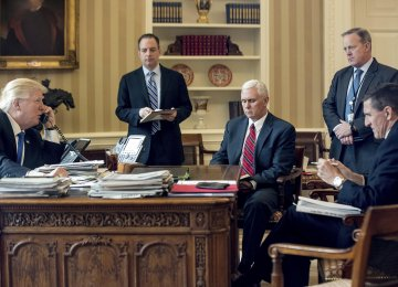 In this Jan. 28 file photo, President Donald Trump (L) speaks on the phone with Russian President Vladimir Putin, while  (from 2nd L to R) Chief of Staff Reince Priebus, Vice President Mike Pence, White House Press Secretary Sean Spicer and  National Security Adviser Michael Flynn look on at the White House, Washington.