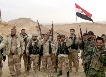 Syrian soldiers flash the victory sign.