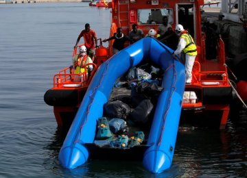Migrants intercepted aboard a dinghy off the coast  in the Mediterranean Sea help rescuers unload their dinghy from a rescue boat after arriving at the port  of Malaga, southern Spain, on July 7.